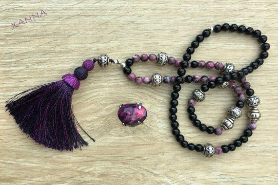 COLLAR: cuentas de jaspe sésamo fúcsia y ónix negro, con abalorios plateados y borla a conjunto con la borla de tonos fúcsia. - cuentas: jaspe sésamo fúcsia (8 mm) y ónix negro (8 mm). - borla: decorativa tonos fúcsia (10 cm) Largo total del collar con borla: 50 cm.   ANILLO: ágata tonos fucsia y negro, del mismo tono que el collar, con cierre adaptable
