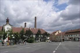 Esto es la plaza. Es grande y está en el centro  de Zbraslav. Hay un banco, una farmacía, un  castillo y muchas tiendas. Es grande y en la plaza  estamos las paradas de autobus.