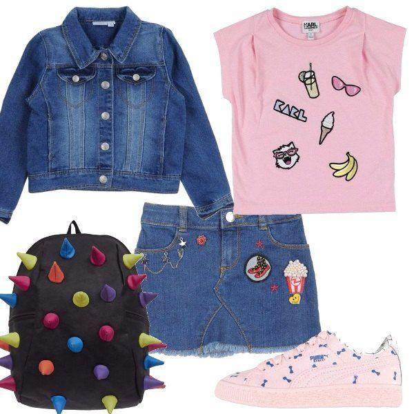 Look composto da gonnellina di jeans con patches e perline, t-shirt a manica corta rosa con stampe e giacca di jeans. sneakers rosa con fiocchetti azzurri e infine zainetto nero a fantasia multicolor.