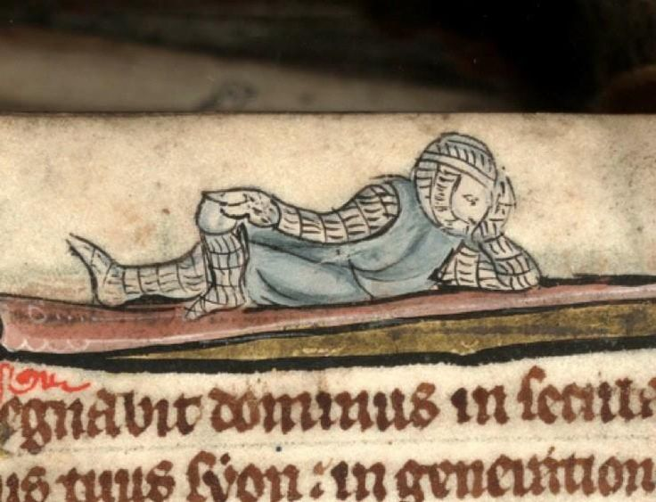 Armored knight wearing a tabard lounges atop a decorated border in the top margin of a medieval manuscript. DOUAI, Bibliothèque municipale, 0193