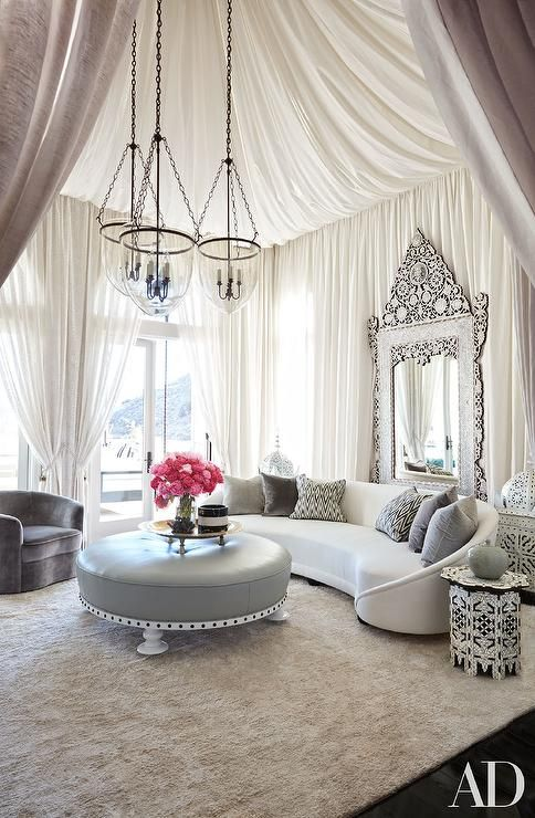Khloe Kardashian - Hollywood regency style living room features the ceiling and walls clad in white cloth panels lined with with a full length ornate mirror, Levantine Mirror, placed behind a vintage curved white sofa by John Salibello accented with gray pillows facing a round gray leather ottoman illuminated by three glass lanterns.