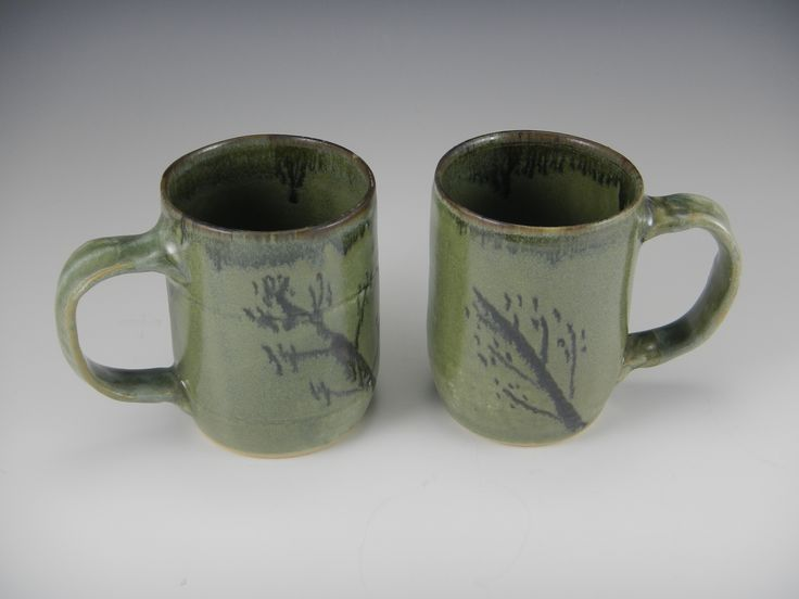 "A good pair of mugs for contemplative moments with tea or coffee, these warm-jade-colored mugs are decorated with a touch of the winter woods. Each one is 4"" tall."