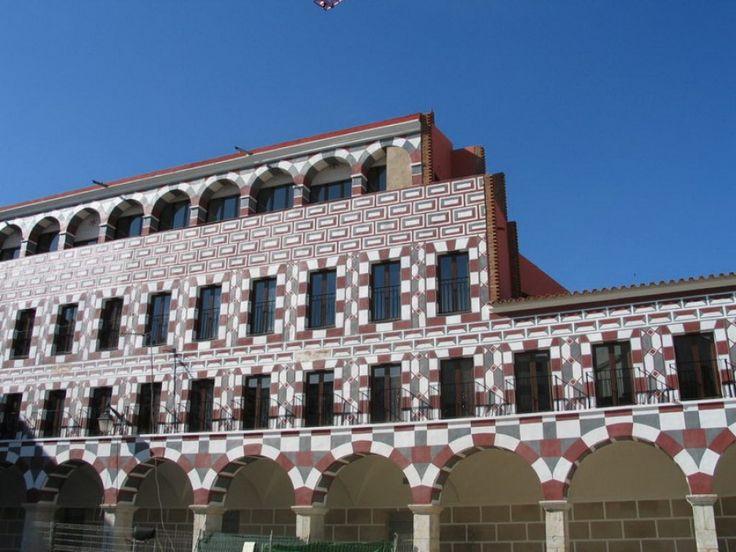 """La Plaza Alta de la ciudad de Badajoz fue antiguamente simplemente """"La Plaza"""", el foco central de la actividad urbana. Bajo estos portales se celebraron los mercados medievales. En sus alrededores se encuentran casas y monumentos notables, como la alcazaba, el Ayuntamiento Viejo, las Casas Coloradas, las Casas Mudéjares o la Torre de Espantaperros."""