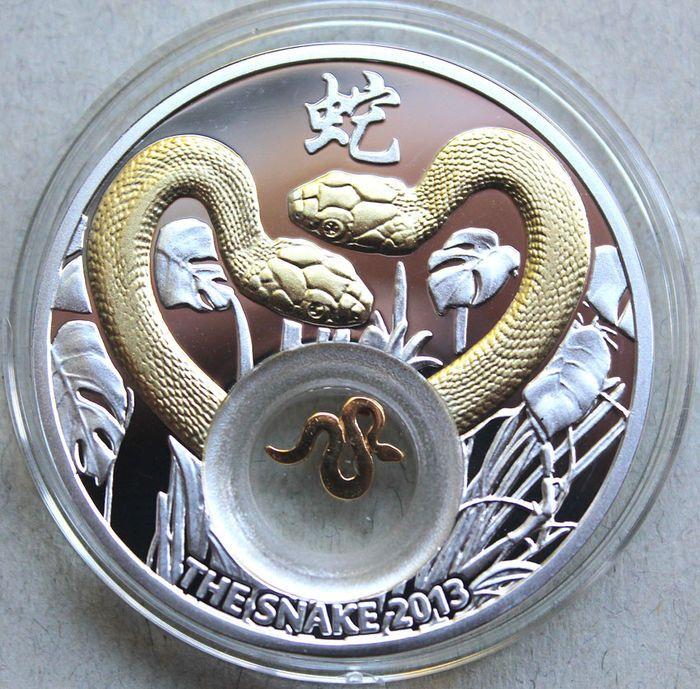 """Niue - 1 dollar 2012 """"The Snake"""" - zilver  De slang 2013 - 2013 van de Chinese dierenriem kalender in verband met het """"jaar van de slang""""Voorzijde: Een afbeelding van koningin Elizabeth II met cirkel schrijven en nominale waardeRug: een paar vergulde slangen onder de bladeren en grasSpecial: een kleine Slang-vergulde in de inlayLand van herkomst: NiueNominale: 1 dollarJaar: 2012Materiaal: Sterling Zilver 925/1000 met 24-karaats gouden toepassingenDiameter: 41 mmGewicht: 28.28 gBewijsOmloop…"""