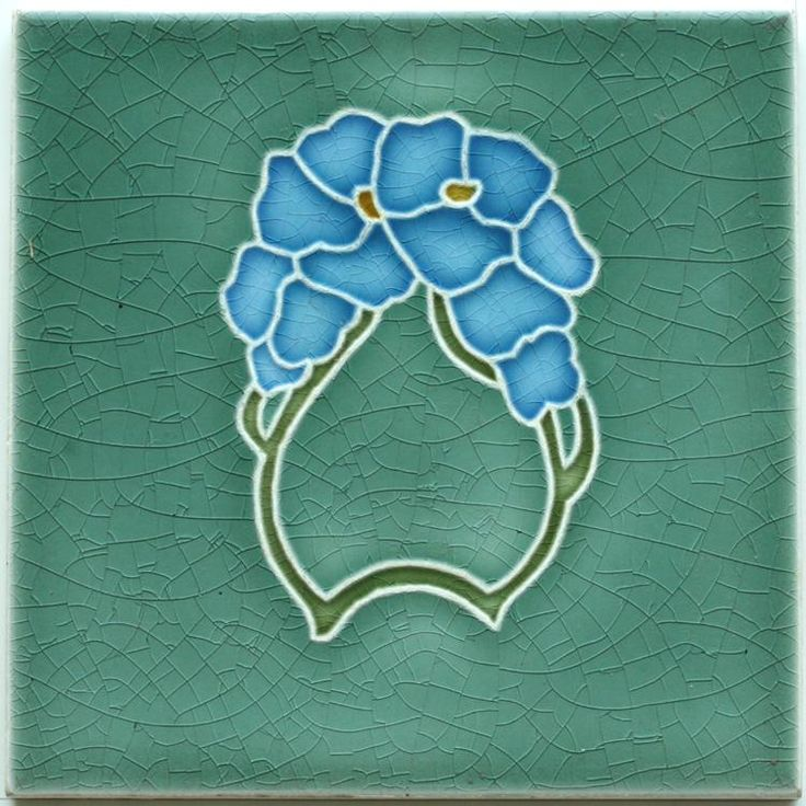 An Art Nouveau tube line tile with stylised pansy design in light blue, green, and white on a light olive-green...