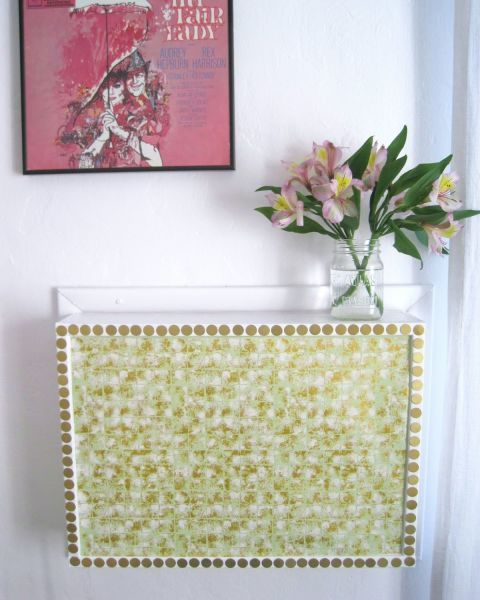 This cover gets pizzazz from a bit of decorative paper, which makes the AC unit blend seamless into this blogger's gallery wall.