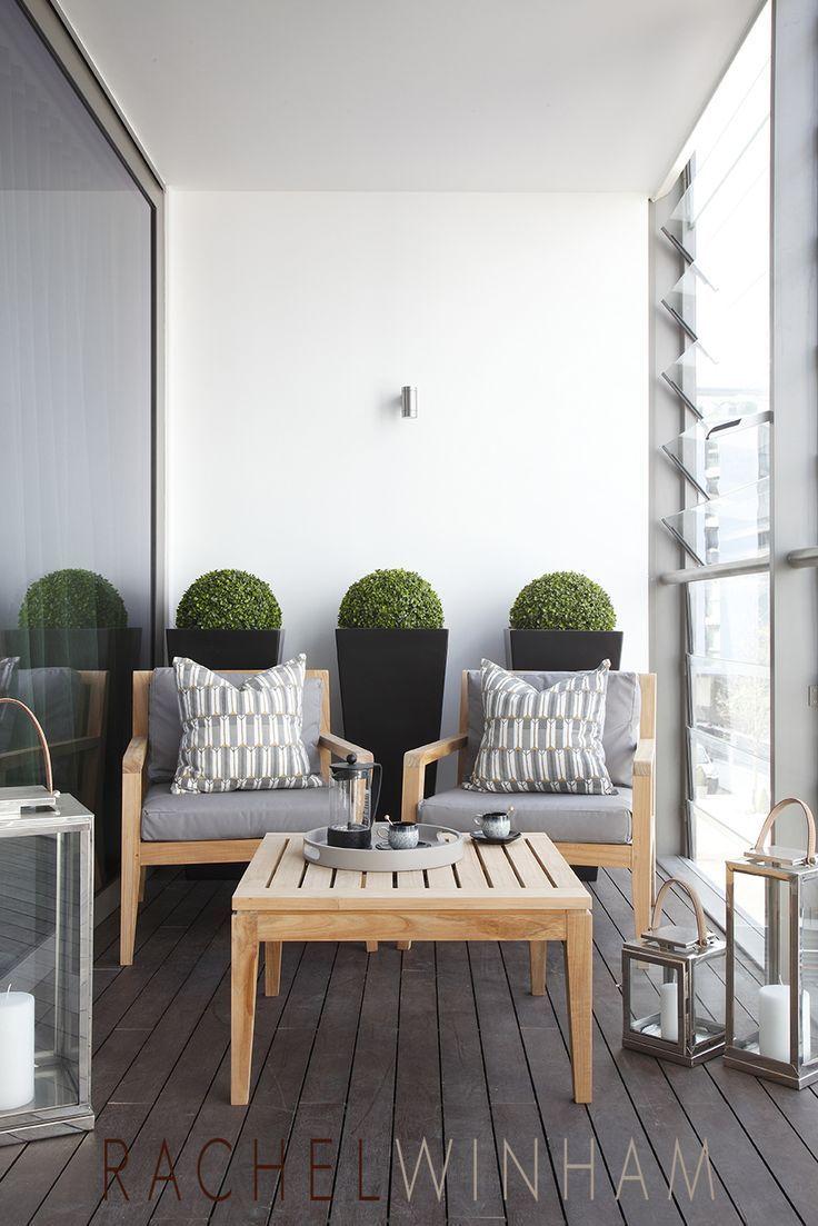 petit coin salon dans le jardin: hauts pots de fleurs similaires avec des buissons, 2 fauteuils, des coussins et une petite table basse