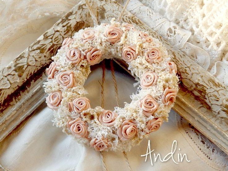 Růžičkový věneček Věneček ve styu shabby chic je bohatě zdoben saténovými růžičkami starorůžové barvě. Závěsné poutko z režného provázku dává vyniknout něžným kvítkům zasazeným do vypichované krajky. Průměr 10 cm