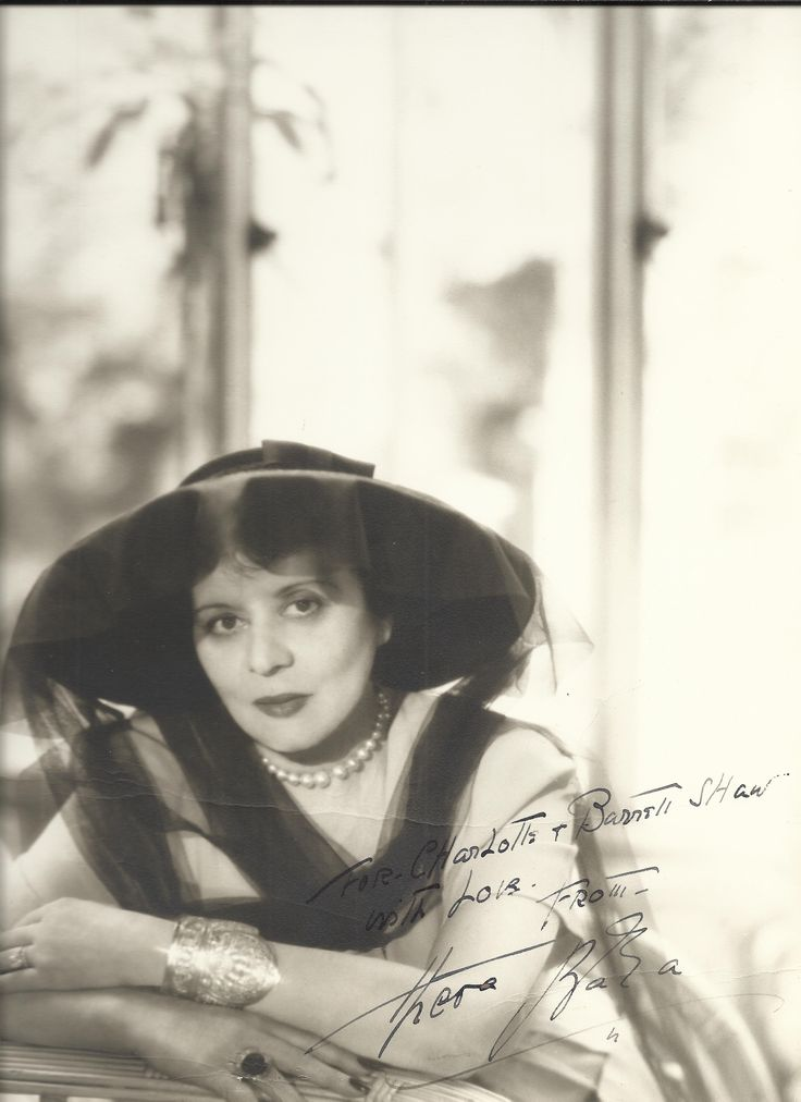 BARA THEDA: (1885-1955) American Actress of the Silent screen. Vintage signed and inscribed 10.5 x 13.5 photograph of The Vamp in a half length pose wearing a wide brimmed black hat and lace veil. Signed in dark fountain pen ink to a clear area at the base of the image, 'For Charlotte & Barrett Shaw, with love from Theda Bara'.