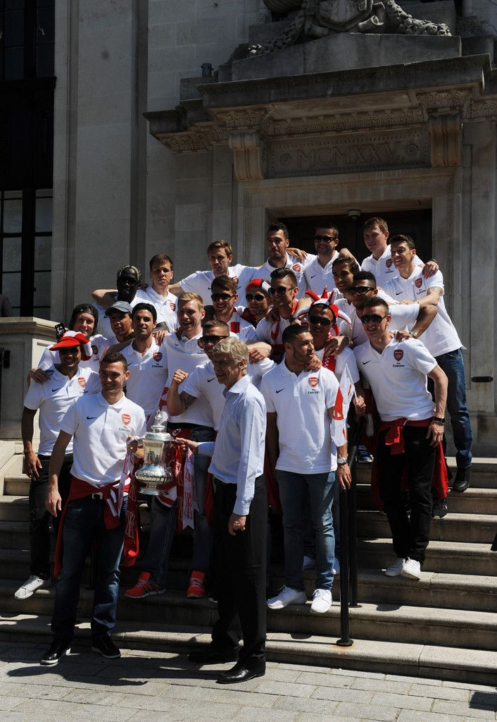 The Arsenal FC players pose with the FA Cup on the steps of Islington Town Hall during the Arsenal FA Cup Victory Parade in Islington, London. (18 May 2014)