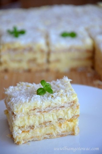 View photo Rafaello without baking [sheet measuring 25 cm by 30 cm] Ingredients: approx. 450 g biscuits (3 layers) 3 cups milk 3/4 cup sugar 2 teaspoons vanilla sugar 3 heaped tablespoons cornstarch 3 heaped tablespoons of flour 250 g butter, 50 g white chocolate 1 cup desiccated coconut Upper: 50 g white chocolate 1/2 cup desiccated coconut cream pudding: Half pour the milk into a saucepan and bring to boil.  The rest of the milk mix with sugar, vanilla sugar and wheat flour and potato…