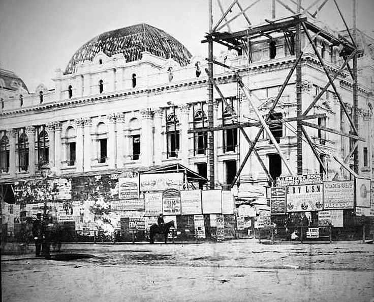 The construction of Melbourne Town Hall {ca: 1870} - note grocery store on site of Manchester Unity Building.