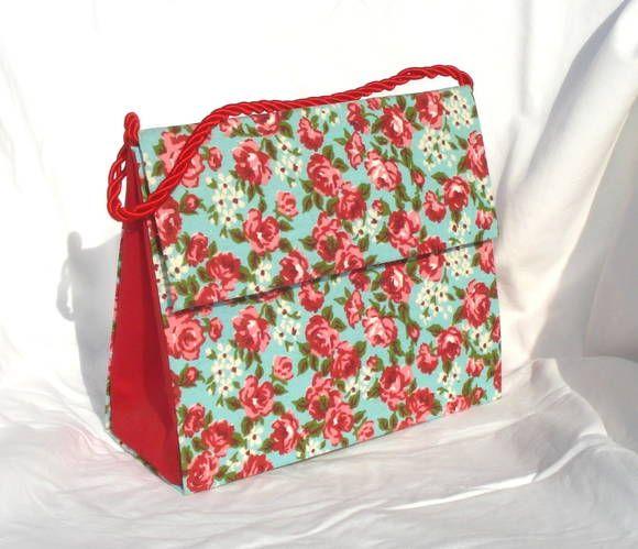 Bolsa de mão cartonada com alça em cordão acetinado com estampa floral de fundo azul e interior e laterias vermelhos. R$ 65,00