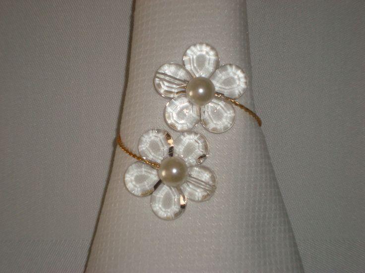Porta-guardanapo confeccionado com peças de acrílico transparente, pérola e arame prateado ou dourado <br>A florzinha tem 3,0cm <br> <br>Venda mínima: 10peças.