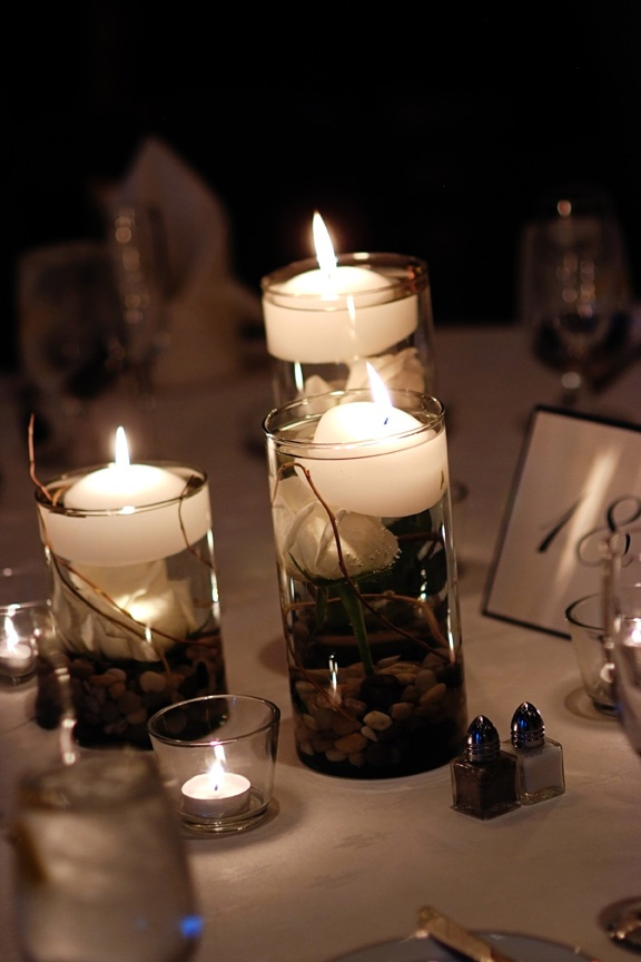 Pebbles white rose and floating candle in glass cylinder for Glass tables for wedding reception