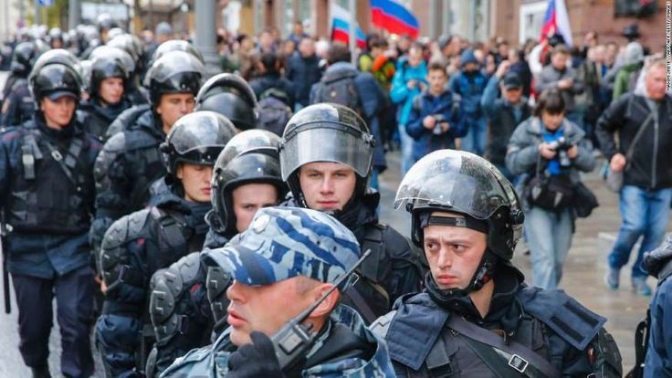 290 arrests in anti-Putin march on Russian leader's birthday   -  October 8, 2017:      Riot police follow protesters in Moscow on Saturday.