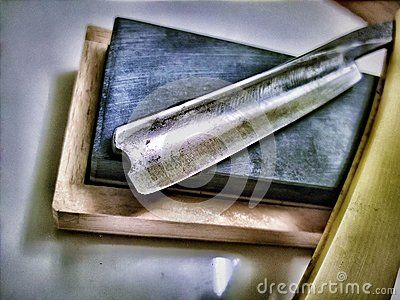 A shot of my straight razor, open blade, sitting on a wooden box, edited.