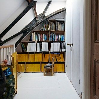 The bookshelf-in-an-alcove idea highlights the sturdy architectural beams beautifully.