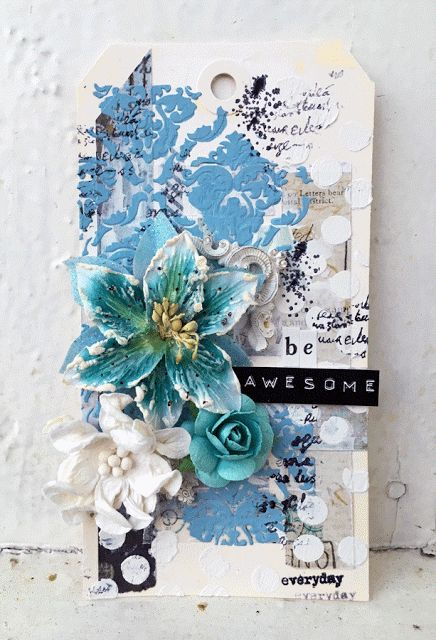 Tag with gesso, scraps of paper, paste, paint + stencils, flowers and resin embellishments.
