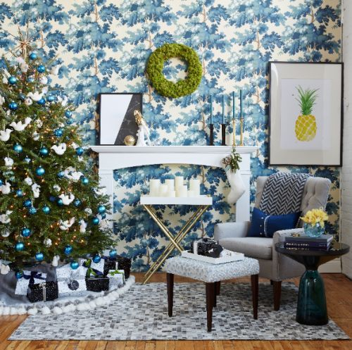 Your Christmas decor should never compete, but accent! Love the choice of blue & white ornaments to complement the wallpaper. The faux fireplace is a nice touch!