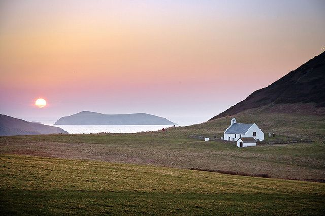Church of the Holy Cross - Sunset view with Cardigan Island in background. Wales