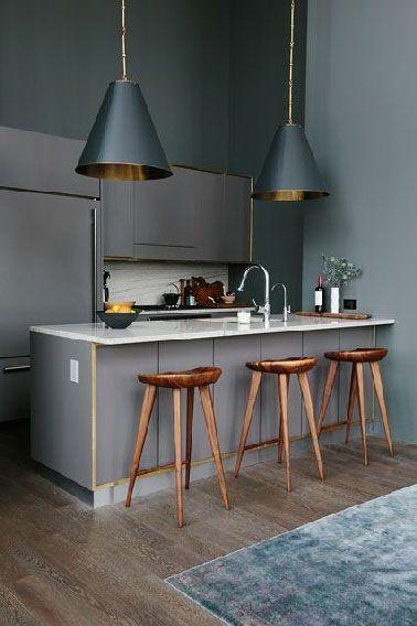déco cuisine entièrement grise en trois tons. meubles gris souris intégrés dans mur peint gris anthracite. Au dessus du bar souligné de baguettes de laiton, 2 big suspensions avec abat-jour cuivre