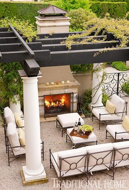 A fireplace and overhead protection from wind and rain help extend the time spent relaxing in this lovely outdoor space. - Traditional Home ® / Photo: John Granen / Design: David Pfeiffer