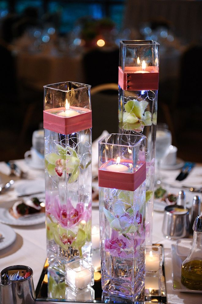 Submerged orchids, floating candles, small votives. I like the addition of the ribbon around the vases.