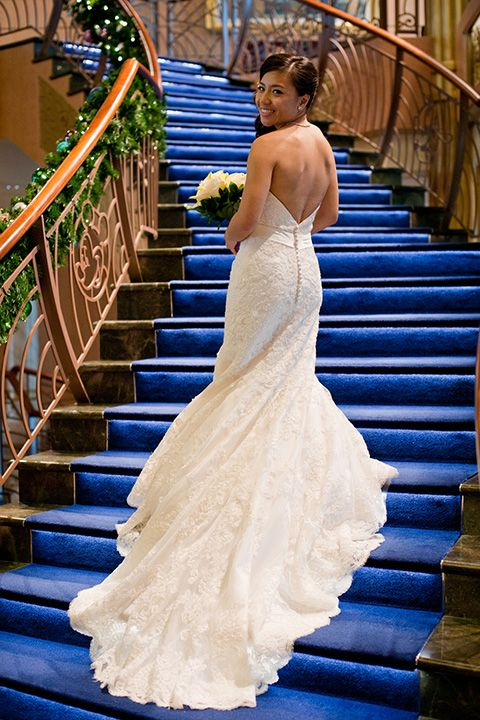 A Disney Cruise Line bride displays her beautiful wedding dress on the grand staircase