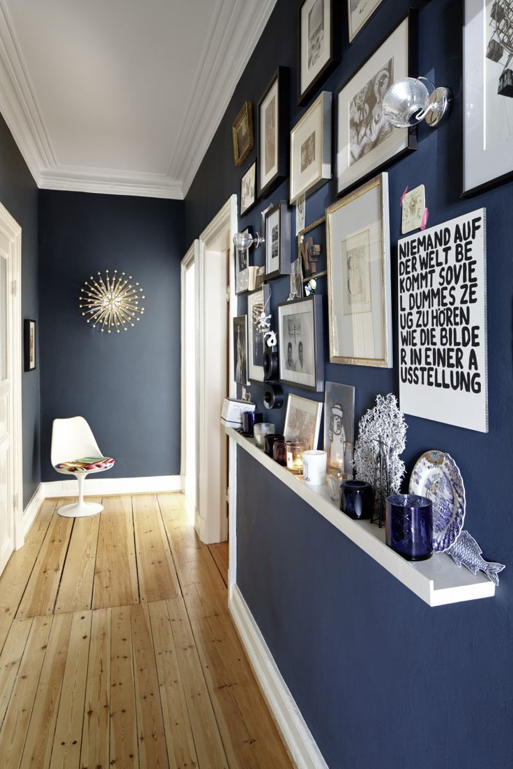 Blue wall with hanging art and shelves