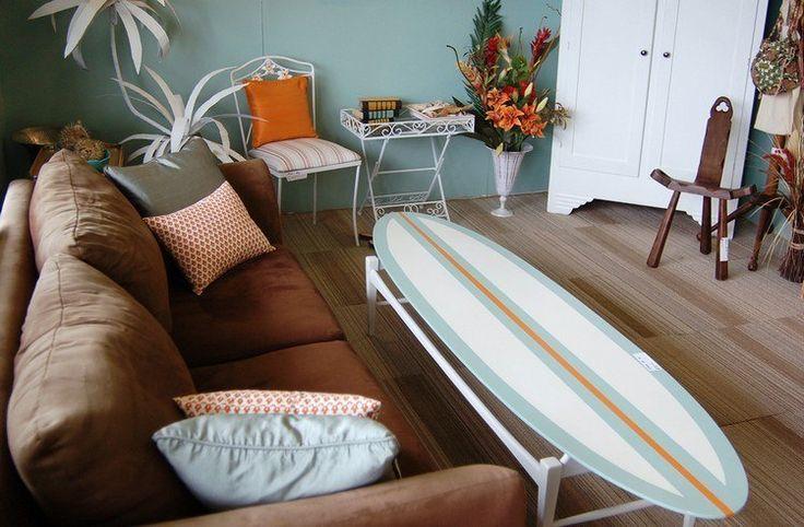 table basse en planche de surf dans le coin de détente avec u canapé droit