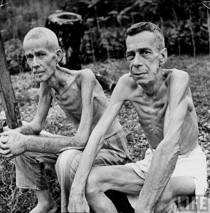 Lee Rogers & John C. Todd sit outside a Japanese prison camp following their release by Allied forces, Manila, Philippines, February 05, 1945
