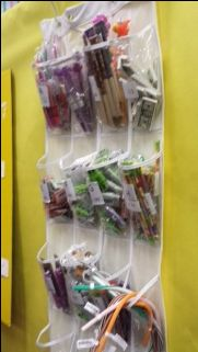 Book Fair Brilliance!  Clear Shoe Rack to hold pens, pencils, and erasers.  Put behind register so kids can see and volunteers have easy access.  Awesome idea, Elaine!