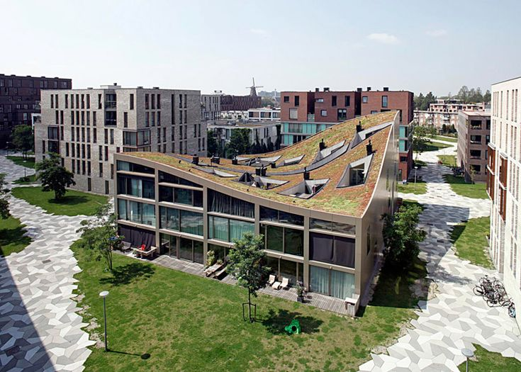 Terraces are carved from the green roof of NL Architects' Funen Blok K