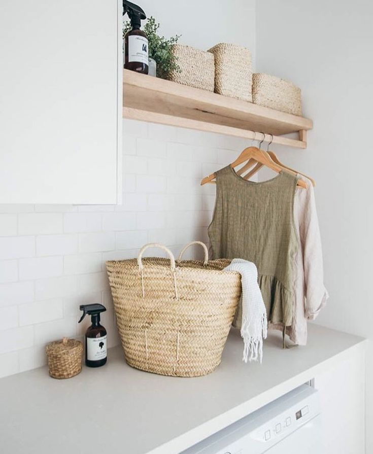 Laundry room inspiration. Wooden shelf with rail underneath for hangers. White subway tile. Wicker storage baskets.