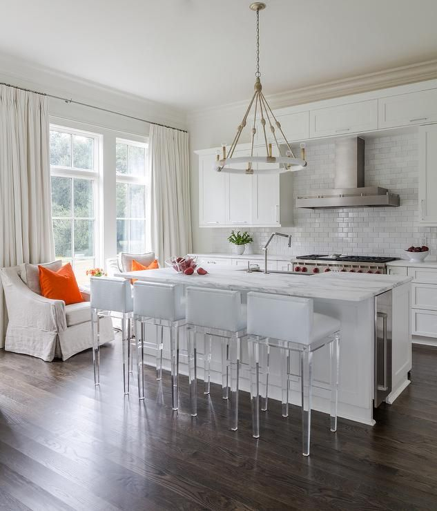A Lowry Pendant hangs over a white center island fitted with a stainless steel…