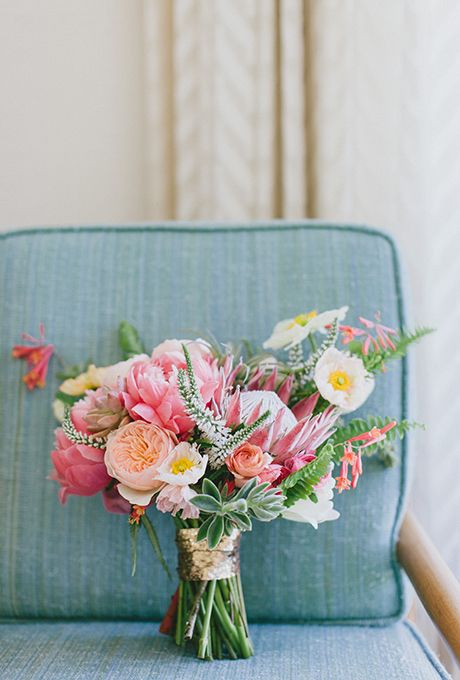 bouquet of coral charm peonies, king proteas, succulents, poppies, honeysuckle, ranunculuses, roses, sword ferns, veronica, and tillandsia