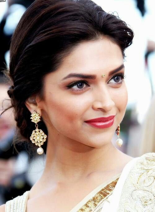 Love Deepika Padukone's makeup. The red lips and winged eyeliner teamed with statement earrings is just perfect.