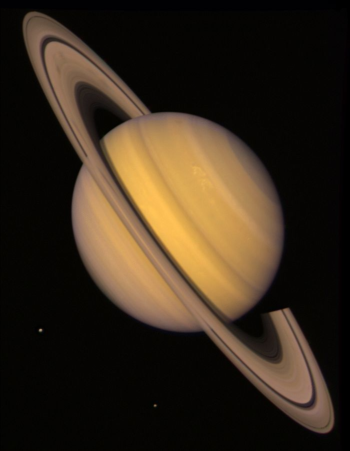 1981: A true-colour photograph of Saturn, taken by Voyager 2 from a distance of 34 million kilometres, shows the moons Rhea and Dione as white dots beneath the planet.  NASA/JPL-Caltech