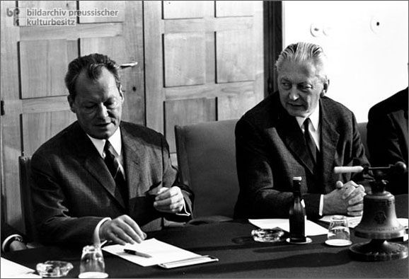 """Kurt Georg Kiesinger and Willy Brandt (1969)-The Grand Coalition from 1966 to 1969 was a temporary """"marriage of convenience"""" between the two great national parties, the CDU/CSU and the SPD. This photograph shows Chancellor Kurt Georg Kiesinger (CDU) (right) with his Foreign Minister and eventual successor, Willy Brandt (SPD) (left), at the last cabinet meeting of the Grand Coalition on September 29, 1969. Parliamentary elections in the fall of 1969 led to a social-liberal coalition between…"""