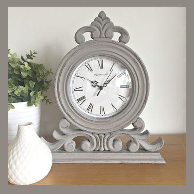 An on-trendgrey mantel clock in a shabby chic design. Roman numerals  Dimensions - 32cm x 30cm x 5cm