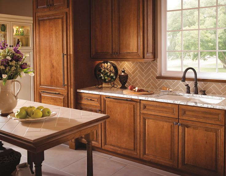Warm wood kitchen gives a traditional aesthetic to a beautiful, bright kitchen, while the patterned subway tiles gives it the modern wow factor. Venetian bronze faucet by Delta Faucet.