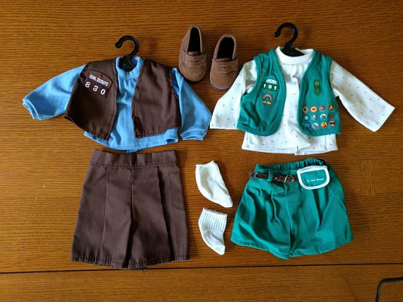 18 inch doll Girl Scout and Brownie Uniform, Doll Girl Scout Outfits, American Girl Doll  Two Girl Scout Uniforms in one set. Brownies and Girl Scouts Uniforms with a pair of brown shoes.  The Girl Scout Uniform was an American Girl of Today outfit released in 1996 and retired in 1999. Retail cost was $22 for the green GS uniform only with other shoes than the ones included here. Since American Girls are intended to represent a girl of about nine years old, this GS uniform represents the…