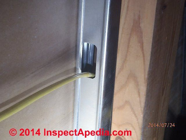 Unprotected NMC wiring passing through a metal stud violates electrical code (C) InspectApedia Bob Sisson
