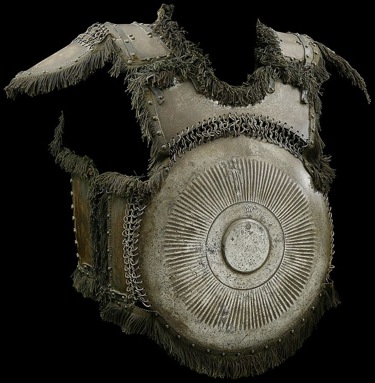 Ottoman krug, 15th/16th c, steel, circular chest plate with St. Irene arsenal mark and back plate with flat central boss bordered by radiating flutes, three smaller plates below the neck and under the arms with riveted and solid rings, back-plate with shoulder-defense and upper arm defenses, an articulated plate below on riveted leather, six smaller side plates all attached by riveted and solid rings, the main edges with riveted green cotton fringes, and domed copper rivets, 44.5 cm. high.