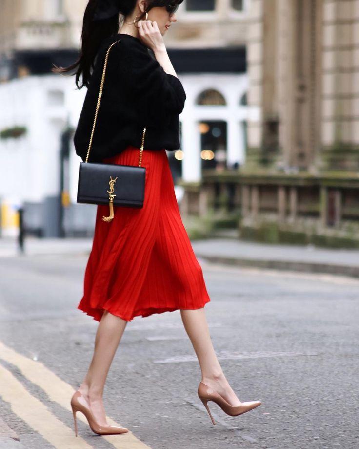 black sweater, red pleated skirt, nude tights & nude heels