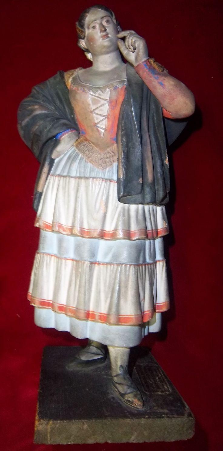 "Barro malagueño de José Cubero (Baena, 1818 - Málaga, 1877) "" Maja - Manola "" Mediados del siglo XIX. Escultura en terracota policromada, base en madera. Medidas: altura 25 cm, base 11 x 8 cm. Conserva la etiqueta del autor."