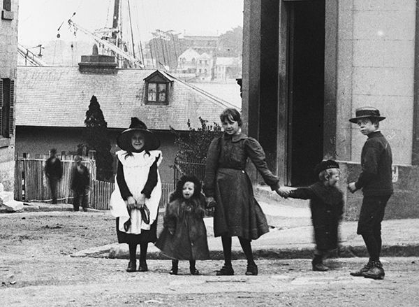 These children were photographed standing outside the White Star hotel on the corner of Bettington and Merriman Streets, Millers Point, in Sydney c. 1901. This photograph appears to part of  the 1901 Rocks Resumption Photographic Survey.  The purpose of the survey was to document the buildings, however, many of the images show people, particularly children, who appear fascinated by the photographer's presence and eager to appear in a photograph.