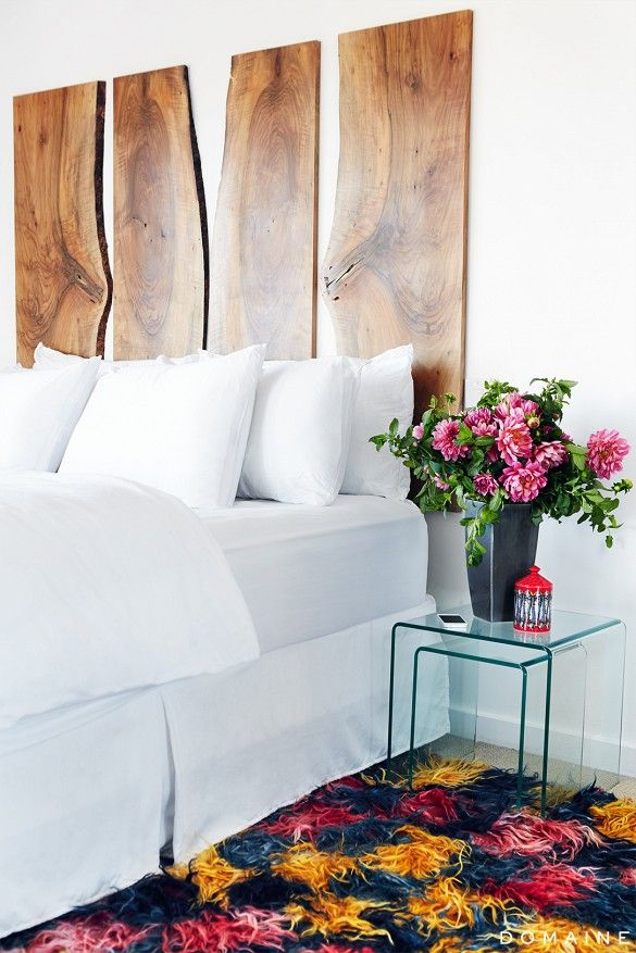 Modern all-white bedroom with raw edge headboard and fresh flowers.