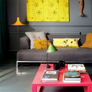 Un salon gris du dupleix londonien, avec une table basse rose et des touches de jaune.